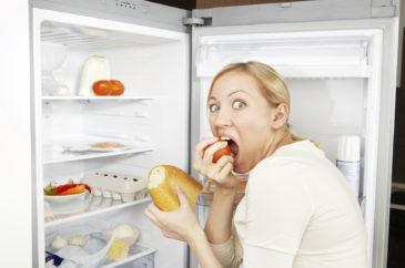 Женщина кушает у холодильника