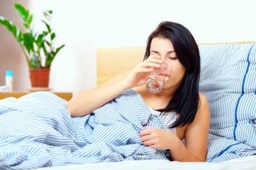 Женщина пьет воду в постели