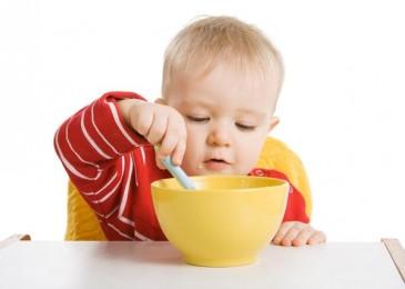 ребенок кушает ложкой