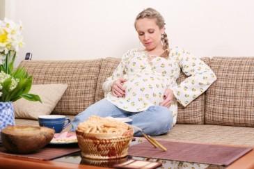 Беременная женщина ест за столом
