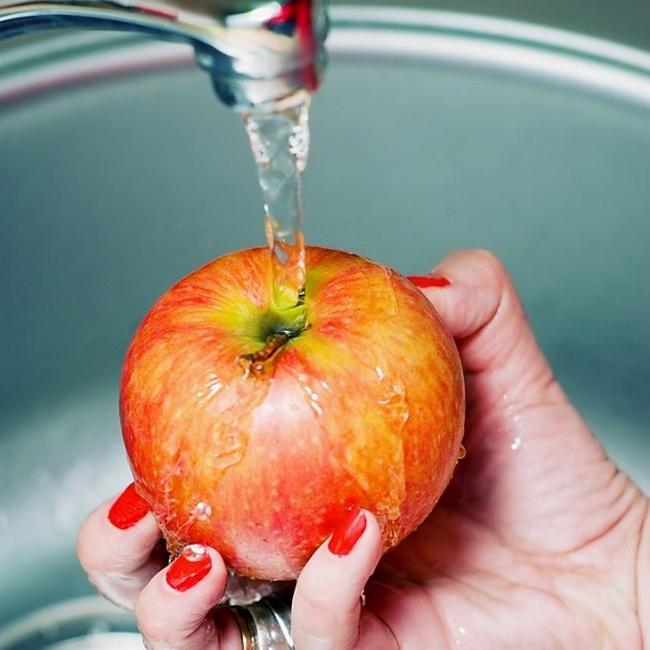 Женщина моет яблоко