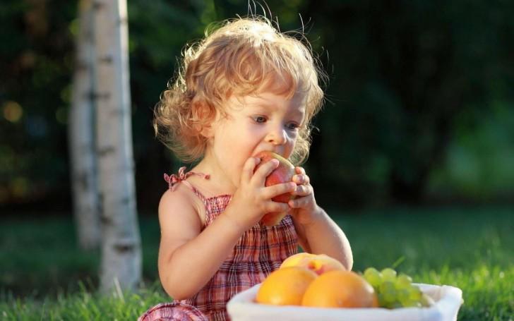 Маленькая девочка есть грушу