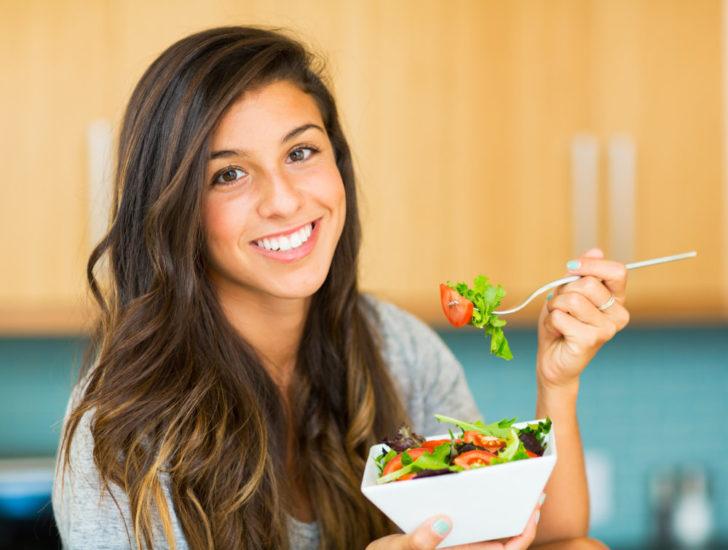 Женщина ест овощи