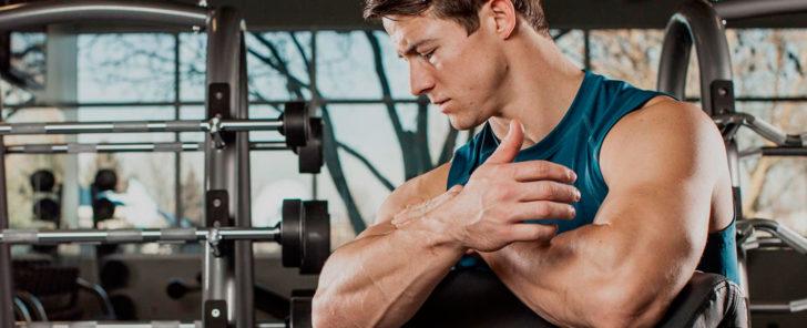Боль в мышцах у мужчины после тренировки в тренажерном зале