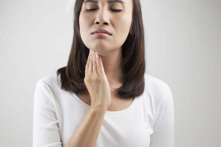 Женщина держится за горло