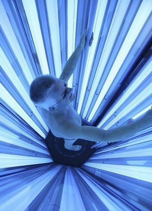 Мужчина в кабине с ультрафиолетовыми лампами