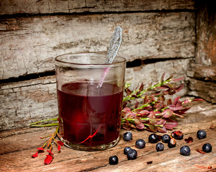 Черничный кисель в стакане и ягоды на столе