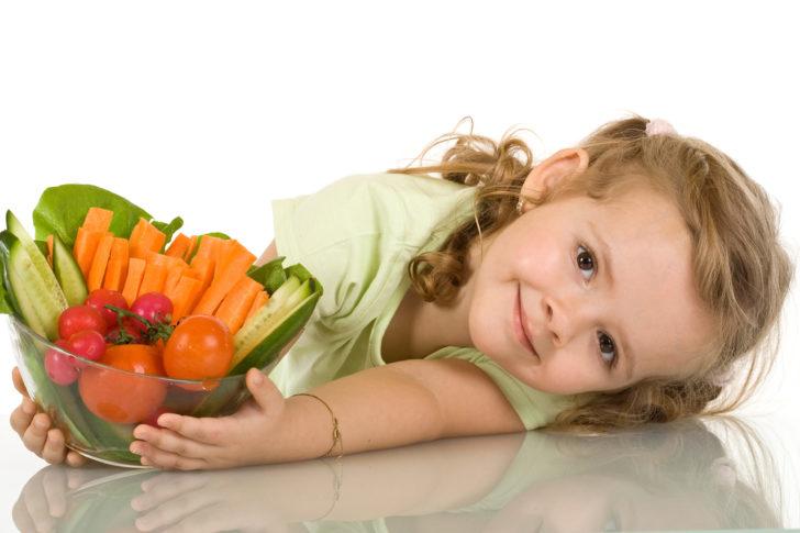 Девочка держит чашку с полезными овощами