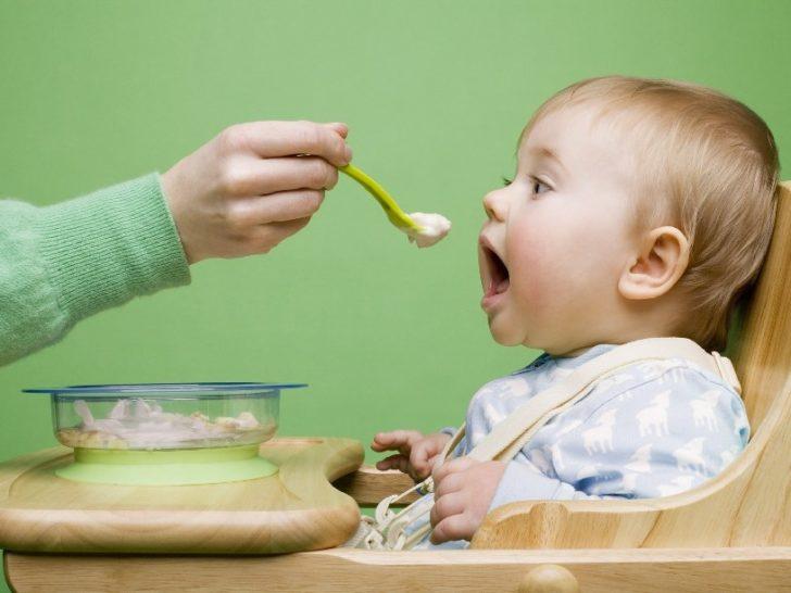 Мама кормит ребёнка кашей с ложечки