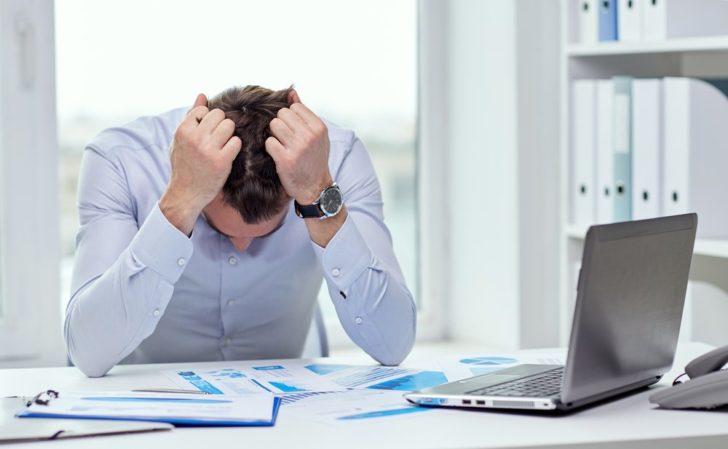 Мужчина испытывает нервное напряжение и держится за голову