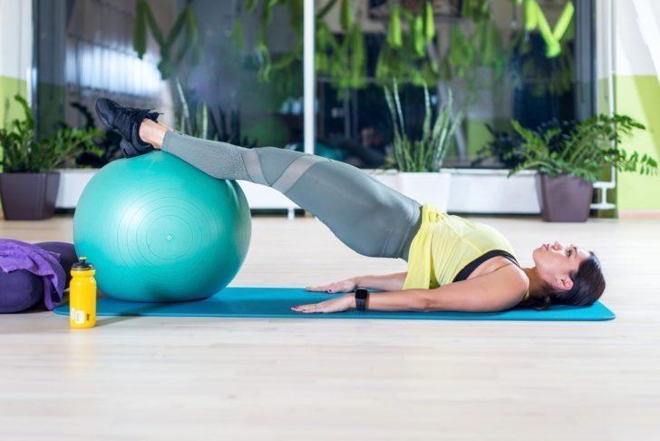 Женщина выполняет упражнение от склолиоза на фитболе