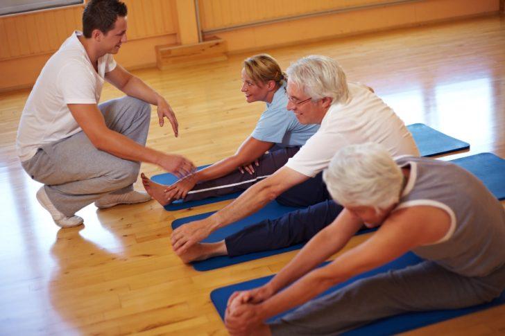 Люди занимаются в спортивном зале с инструктором
