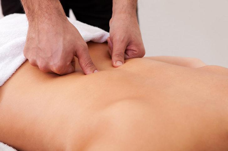 Мужчина выполняет массаж спины