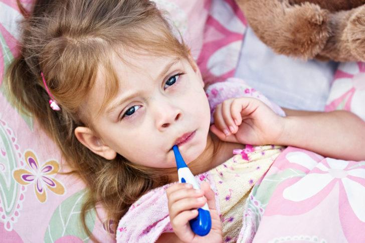Ребёнок, измеряющий температуру тела
