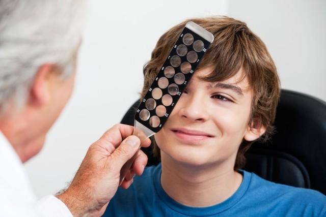 Врач держит линзы у глаза ребёнка