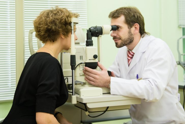 Офтальмолог осматривает глаза пациентки