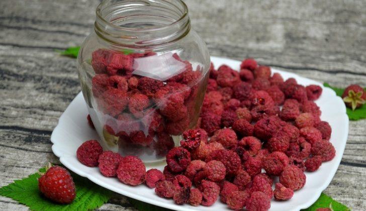 Сушёная малина в банке и в тарелке и ягода свежей малины на листочке