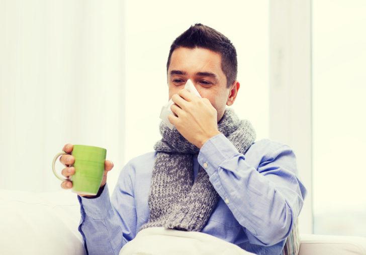 Заболевший мужчина с чашкой в руках