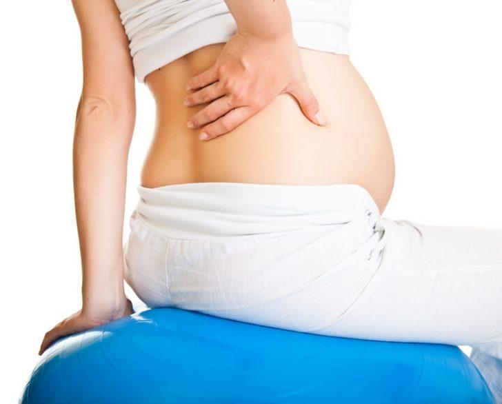 Беременная держится за спину