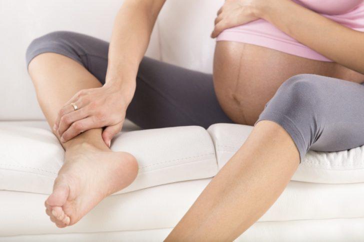 Беременная сидит на диване