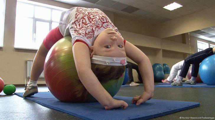 Ребёнок делает гимнастику для укрепления мышц спины