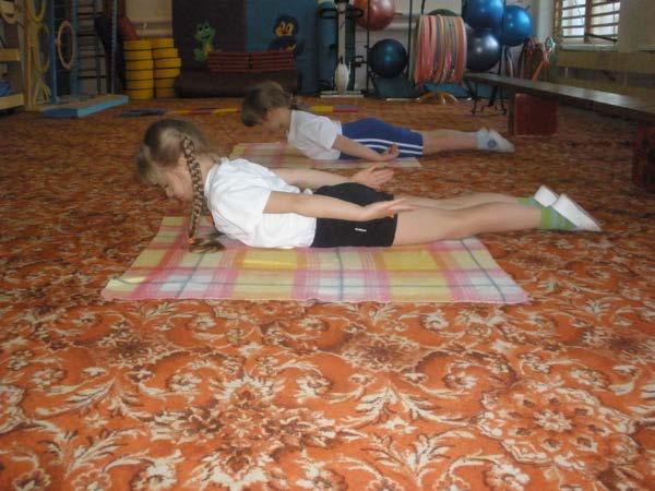 Дети делают упражнение лёжа на животе