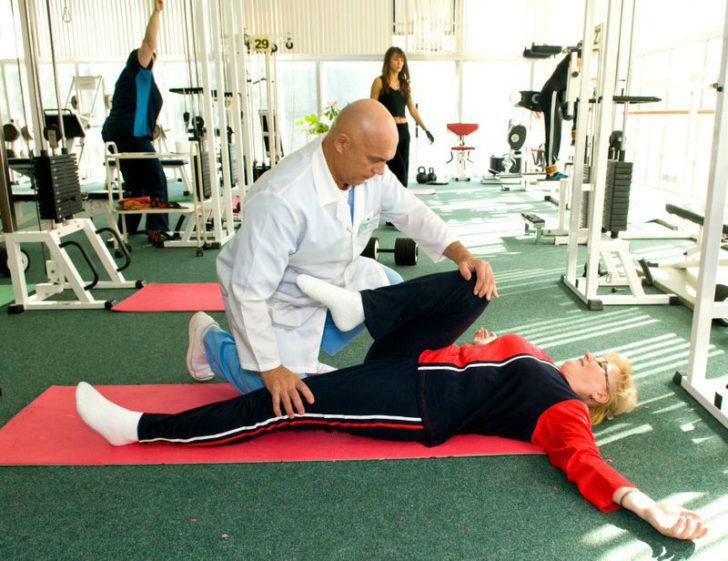 Доктор Бубновский помогает женщине освоить правильность выполнения упражнения