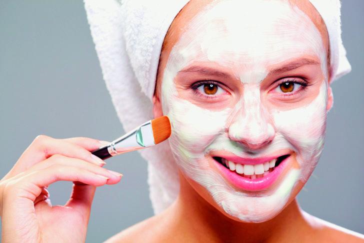 Женщина наносит маску кисточкой