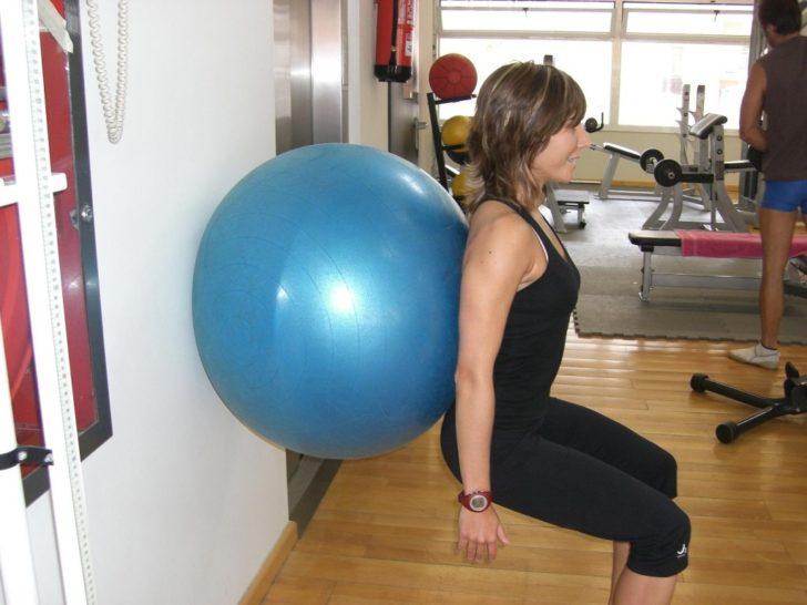 Женщина делает приседания с фитболом