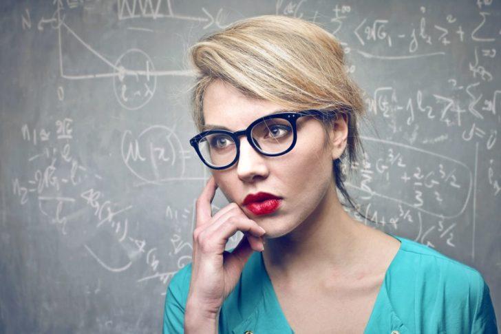Женщина на фоне доски с формулами