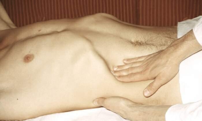 Туловище пациента и рука врача во время пальпации