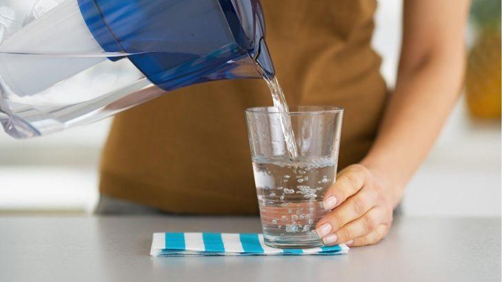 человек наливает воду в стакан