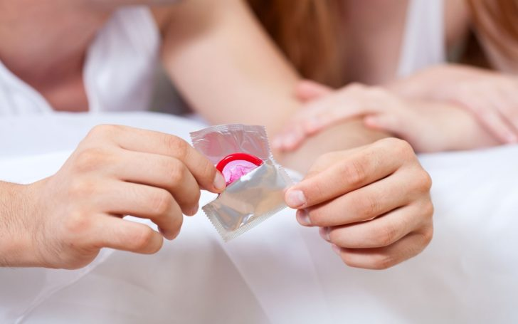 Мужчина держит в руке презерватив