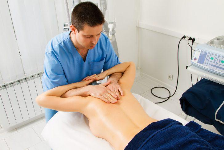 Доктор делает процедуру мануальной терапии