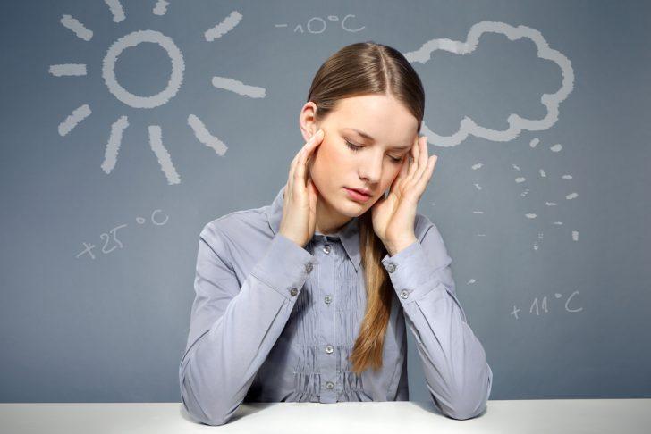 У девушки болит голова из-за смены погоды