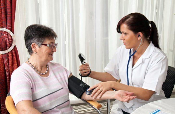 Врач измеряет давление у пожилой женщины