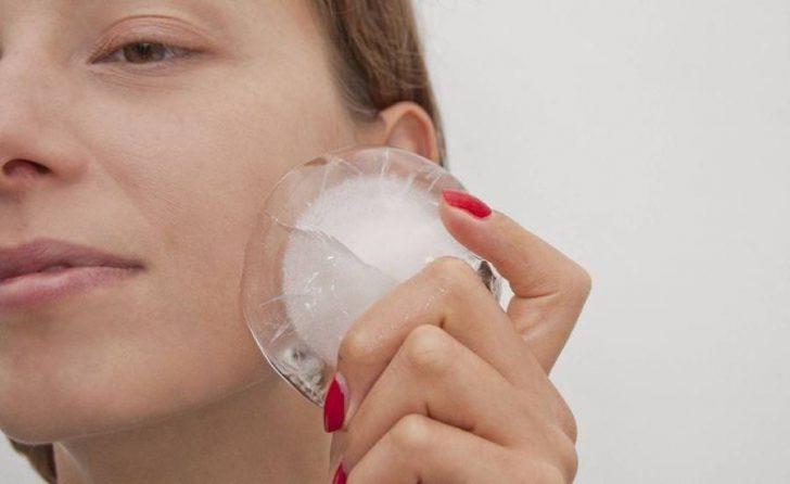 Женщина держит лёд у щеки