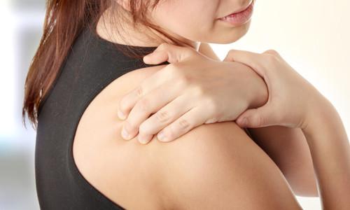 Женщина держится рукой за плечо