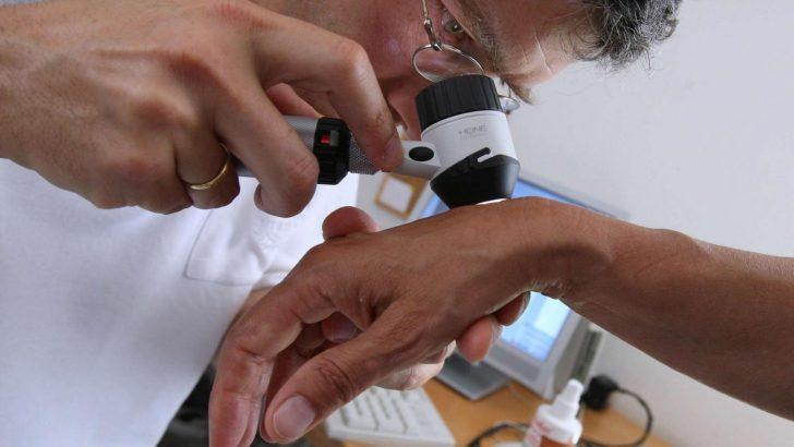 Дерматолог осматривает пациента