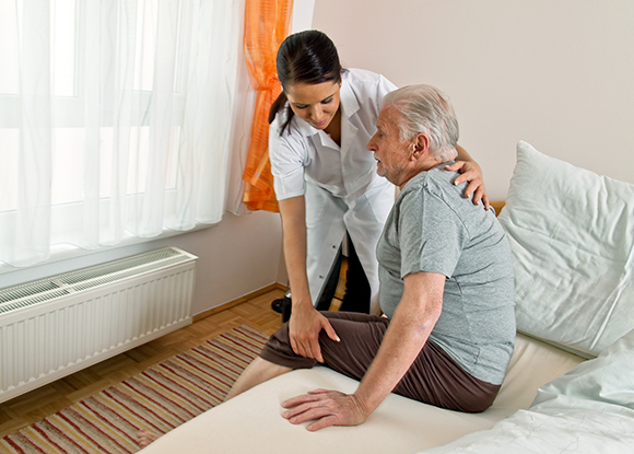 Пожилой мужчина встает с кровати с помощью медсестры