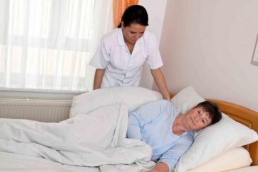 Медработник помогает лежачей женщине